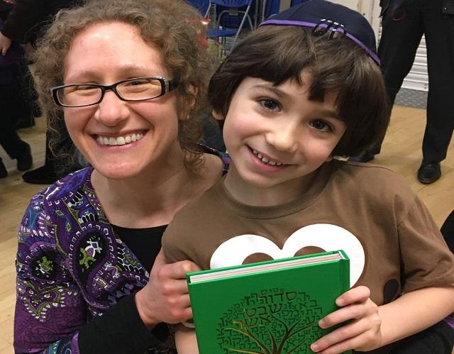 Mum and son holding holding Jewish book