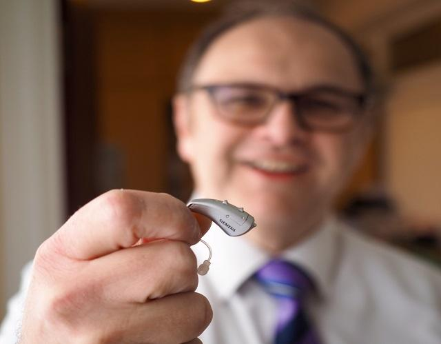 Independent Hearing Aid Specialist showing hearing aid