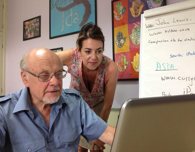 Man sitting at laptop with lady looking over his shoulder